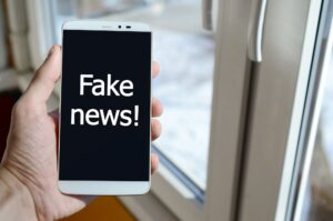 A person sees a white inscription on a black smartphone display that holds in his hand. Fake news!